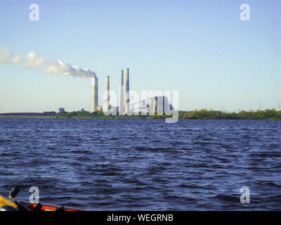 Smoke Emitting From Chimney At Factory By River Against Clear Sky - Stock Photo