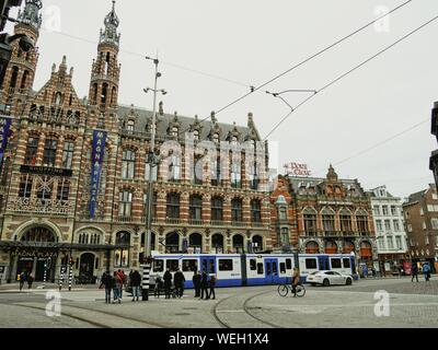 People By Cable Car On Street Against Magna Plaza In City - Stock Photo