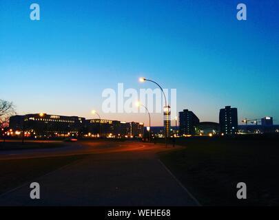 Illuminated City Against Clear Blue Sky At Night - Stock Photo