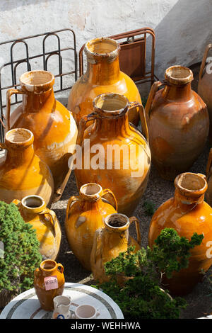 Traditional old pots from Puglia, for storing olive oil and olives,  for sale in an antique shop the town of  Alberobello, Puglia, Italy. - Stock Photo