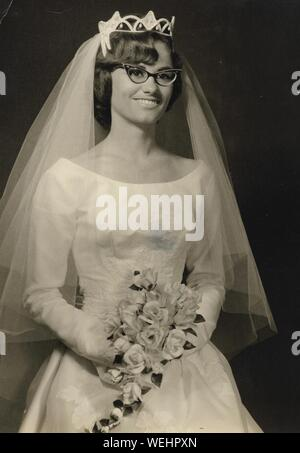 Smiling Bride Wearing Wedding Dress Holding Bouquet While Looking Away - Stock Photo
