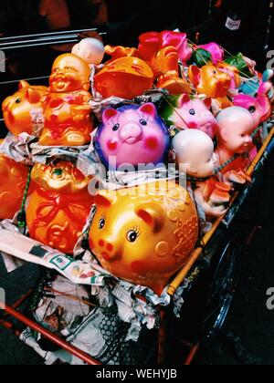 Piggy Bank And Buddha Figurines In Shopping Cart - Stock Photo