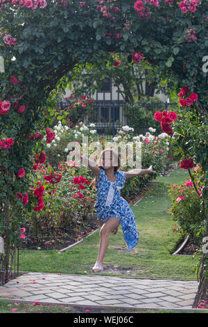 Preteen girl of Asian appearance doing gymnastics in rose garden, San Jose, California - Stock Photo