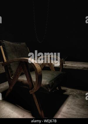 Old Empty Chair Against Black Background - Stock Photo