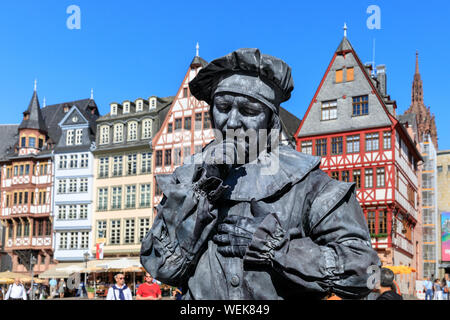 A human statue performer in medieval costume on the Römerberg square with its historic buildings, Frankfurt am Main, Germany - Stock Photo