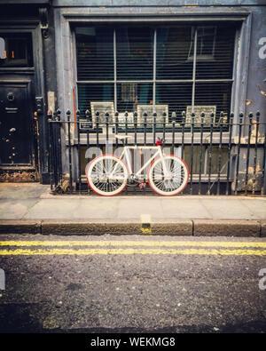 Bicycle Parked Against Railing On Sidewalk - Stock Photo