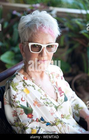 Portrait Of Senior Woman Wearing Eyeglasses Sitting On Chair - Stock Photo