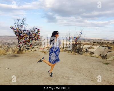 Happy Young Woman Dancing On Field Against Sky - Stock Photo