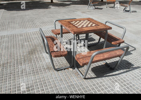 Chequered board game table with seating for players and spectators - Stock Photo
