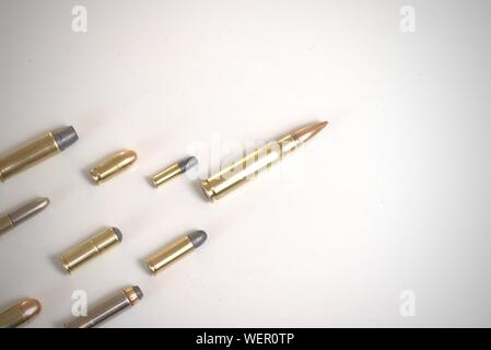 Large bullet leading several smaller bullets laying over a white surface. It works as a concept for leadership, crime, arms race.