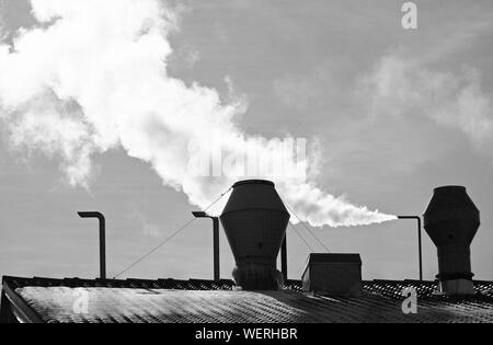 Smoke Emitting From Chimney On Roof Of Factory Against Sky - Stock Photo