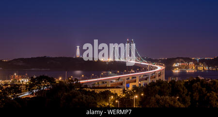 Illuminated 25 De Abril Bridge Over Tagus River By Christ The King Against Sky At Night - Stock Photo