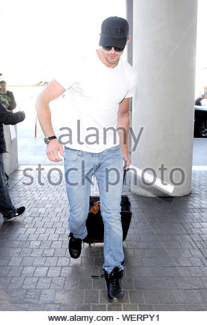 Los Angeles, CA - Alexander Skarsgard looks casual as he takes off from LAX. The handsome actor donned a fitted white t-shirt and blue jeans and toted a small carry on luggage. AKM-GSI March 04, 2014 - Stock Photo