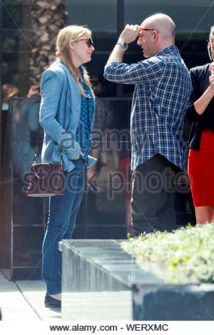 West Hollywood, CA - Actress Kirsten Dunst joins a few friends on their smoke break before heading into a Medical Office on Wilshire Blvd, the blonde actress dressed casual wearing a denim blazer over a blue flower print dress shirt, skinny jeans, black flats and carried a purple leather cross body tote designer bag. AKM-GSI March 5, 2014 - Stock Photo