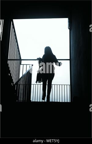 Silhouette Of Woman Descending Stairs - Stock Photo