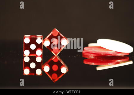 Two Red dice equaling 7 with red and white poker chips on a black reflective background - Stock Photo