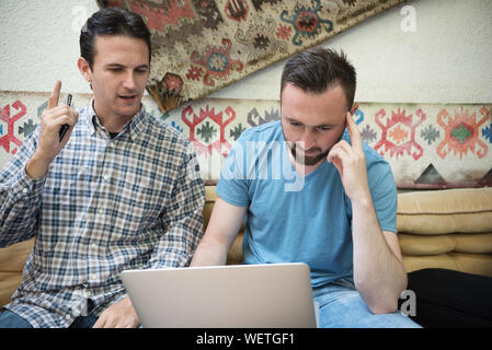 Male Friends Discussing Over Laptop While Sitting On Sofa At Home