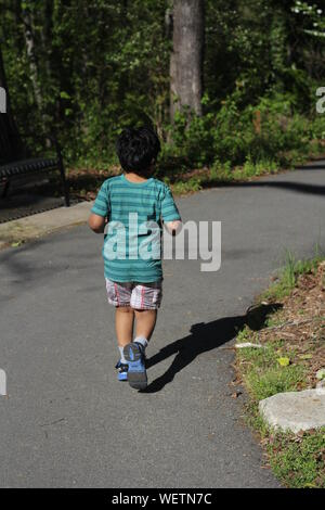 Rear View Of Boy Running On Road Against Trees - Stock Photo