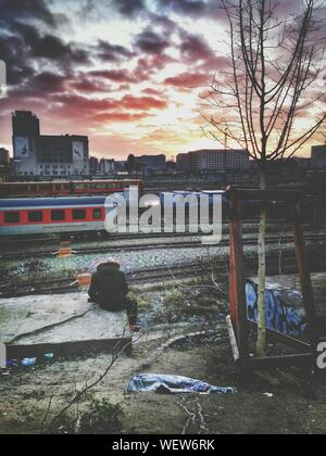 Trains On Railroad Tracks With City In Background - Stock Photo