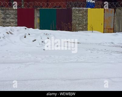 Snow Covered Field Against Colorful Fence - Stock Photo
