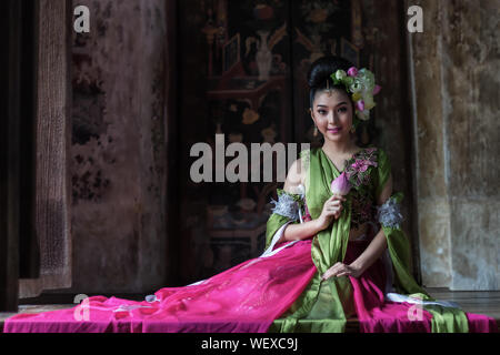 Beautiful Thai woman wearing a national costume and holding a lotus sitting beside a window.Lifestyle and culture of the ancient woman, Thailand. - Stock Photo