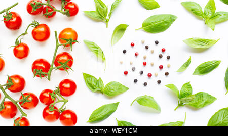 Fresh  cherry tomatoes with basil leaves and different type of peppercorns on white background. Top view - Stock Photo