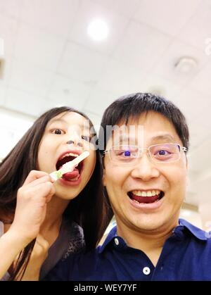 Close-up Portrait Of Father With Cute Daughter Eating Ice Cream At Home - Stock Photo