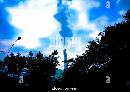 Low Angle View Of Smoke Emitting From Factory Against Cloudy Sky - Stock Photo