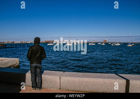 Rear View Of Man Looking Onto Boats In Sea Against Clear Blue Sky - Stock Photo