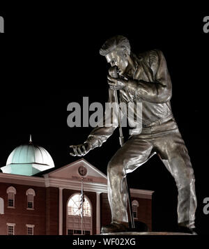Elvis Presley statue in bronze pose with microphone and outstretched hand, at night by the Tupelo City Hall in Tupelo, MS, USA - Stock Photo