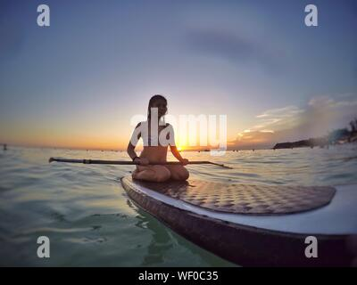 Woman Sitting On Paddleboard At Sea Against Sky During Sunset - Stock Photo