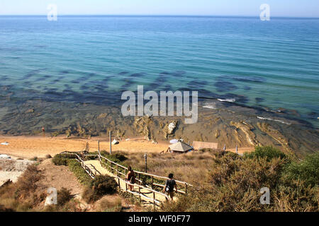Man And Woman Walking On Steps Towards Sea - Stock Photo
