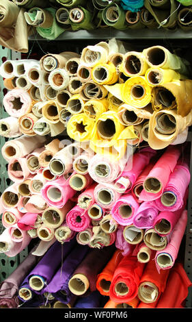 Close-up Of Colorful Fabrics Rolled In Shelves At Store - Stock Photo