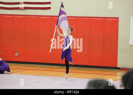 Ballet Dancer Holding Flag While Performing Winter Guard In Gymnasium - Stock Photo