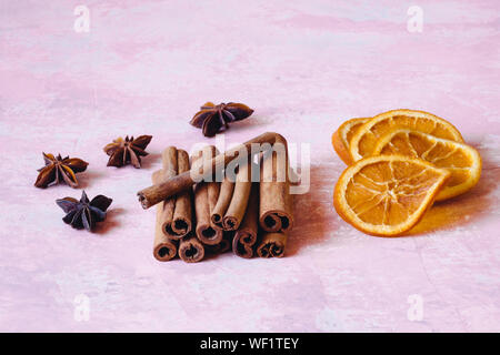 Close-up Of Cinnamon Sticks And Star Anise With Dry Orange Slices On Table Stock Photo