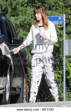 Los Angeles, CA - Actress Dakota Johnson has her hands full as she juggles two coffees along with a bottled juice, a bag of tasty goodies, her wallet and car keys. After putting some of the items away, the pretty brunette walked her dog with her coffee in hand. Now that 'Fifty Shades of Grey' is done filming, Dakota has more time for herself and attended the 2014 Petty Fest last week but did not perform. The much anticipated movie hits theaters in February 2015. AKM-GSI April 7, 2014 - Stock Photo