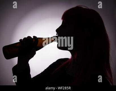 Side View Of Silhouette Woman Having Drink - Stock Photo