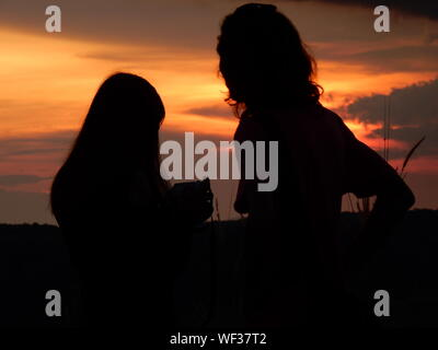 Silhouette Woman Photographing Against Sky During Sunset - Stock Photo