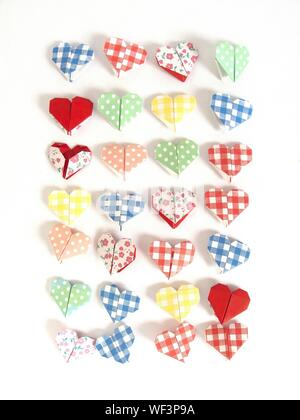 High Angle View Of Folded Paper Hearts Against White Background - Stock Photo