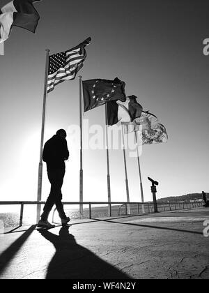 Silhouette Man Walking On Bridge By Various Flags Against Sky During Sunny Day - Stock Photo
