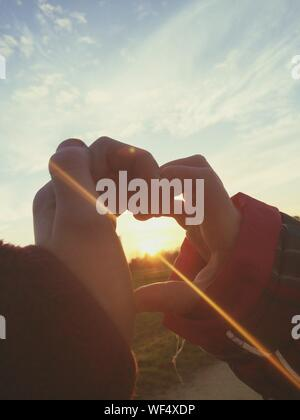 Close-up Of Children Making Heart Shape With Hands During Sunset - Stock Photo