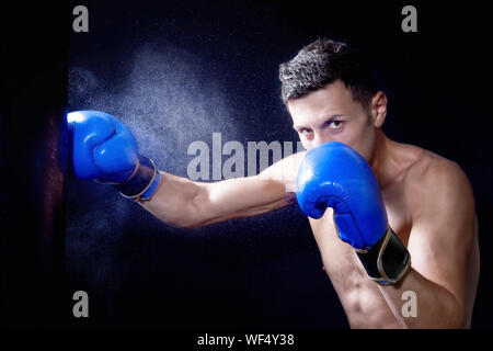 Portrait Of Young Male Boxer Punching Bag Against Black Background - Stock Photo