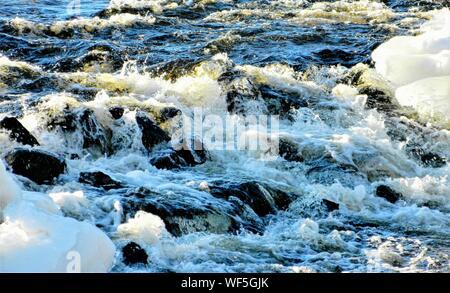 High Angle View Of Waves Splashing On Rocks - Stock Photo