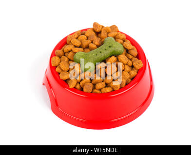 Red pet feeder. Bowl filled with dried food. Kibble on isolated white background