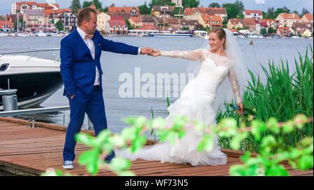 Wedding Couple Holding Hands While Standing On Wooden Jetty At Mikolajki - Stock Photo