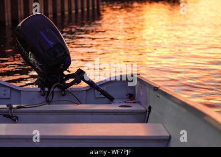 Middletown, CT / USA - June 7, 2019: Boat with an outboard motor parked near the marina at sunset - Stock Photo