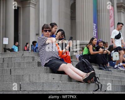 Ney York City, NY / USA - June 28, 2019: Caucasian woman taking a break on the front stairs of the Met along with other tourists - Stock Photo