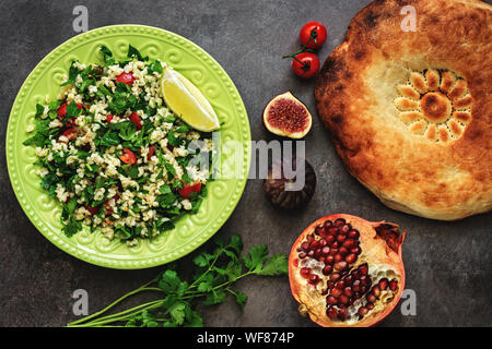 Levantine vegetarian salad with bulgur, parsley, tomato. Middle eastern and arabic salad tabbouleh , pita bread, pomegranate, figs, on a dark rustic b - Stock Photo