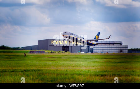 LONDON STANSTED AIRPORT, ESSEX / UK - CIRCA JULY, 2019: Ryanair Boeing 737 takes off with visible Ryanair hangar in background - Stock Photo