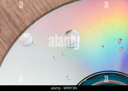 Water drops on a broken data storage optical disk - Stock Photo